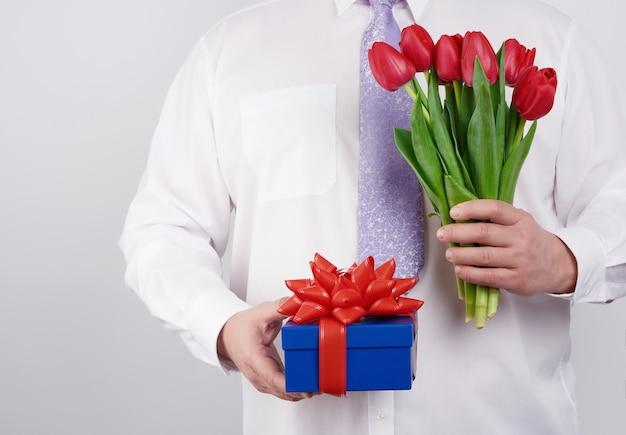 Volwassen man in een wit overhemd en een lila stropdas met een boeket van rode tulpen met groene bladeren en geschenkdoos op een witte achtergrond, concept voor gelukkige verjaardag, jubileum, valentijnsdag