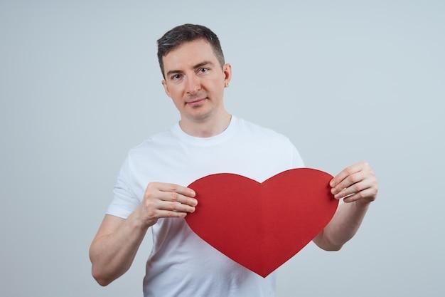 Volwassen man in een wit t-shirt, met een hart van papier in zijn hand, op een grijze achtergrond. fijne valentijnsdag. wereldhartdag.