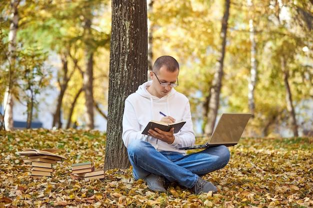 Volwassen man in een witte hoodie studeert in het park op een laptop, schrijft in een notitieblok, leest boeken en leerboeken. buiten leren, sociaal afstand nemen