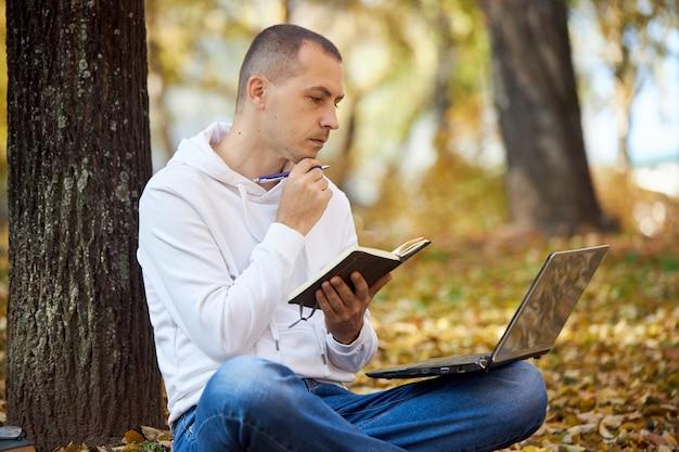 Volwassen man in een witte hoodie studeert in het park op een laptop, schrijft in een notitieblok, leest boeken en leerboeken