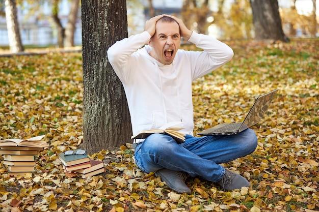 Volwassen man in een witte hoodie studeert in het park op een laptop, schrijft in een notitieblok, leest boeken en studieboeken. buiten leren, sociaal afstand nemen