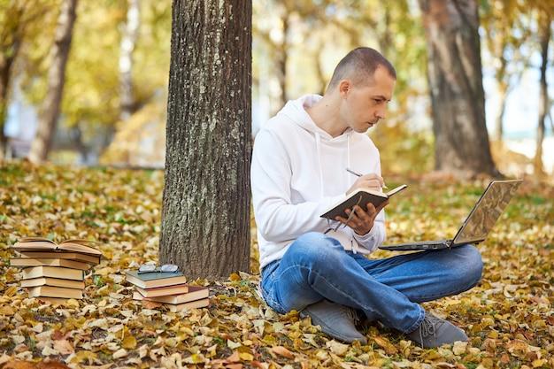 Volwassen man in een witte hoodie studeert in het park op een laptop, schrijft in een notitieblok, leest boeken en studieboeken