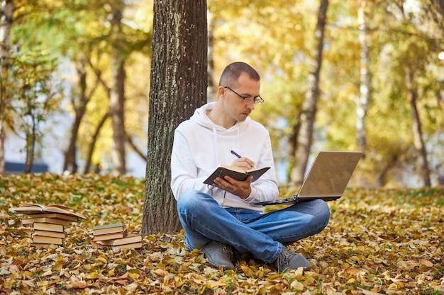 Volwassen man in een witte hoodie studeert in het park op een laptop, schrijft in een notitieboekje, leest boeken en studieboeken. buiten leren, social distancing
