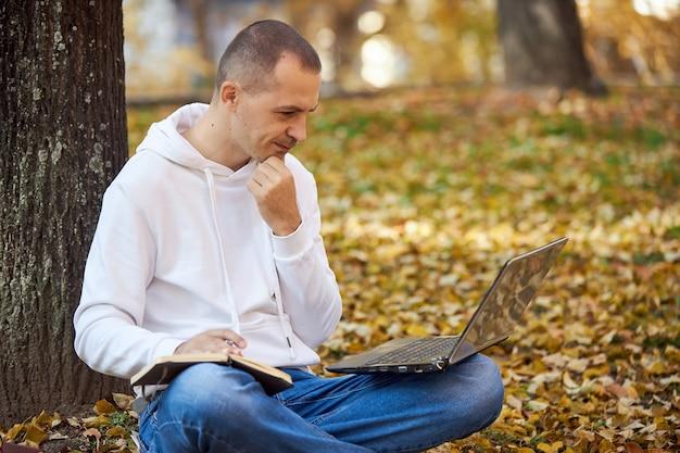 Volwassen man in een witte hoodie studeert in het park op laptop, schrijft in notitieblok, leest boeken en leerboeken
