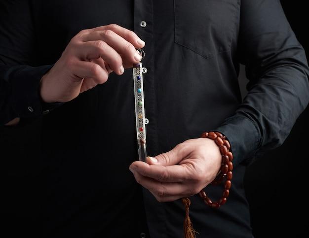 Volwassen man in een zwart shirt heeft een kristallen chakra staaf ingelegd met halfedelstenen