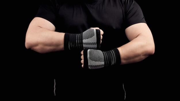 Volwassen man in een zwart uniform en gespierd lichaam staat in een sportieve houding