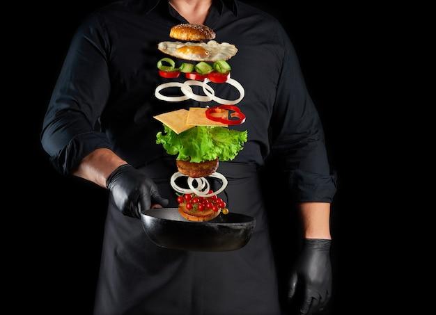 Volwassen man in een zwart uniform met een gietijzeren ronde koekenpan met zwevende cheeseburger ingrediënten