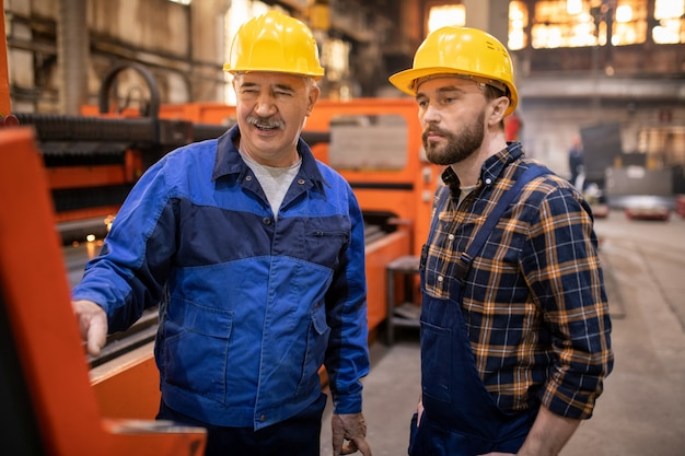 Volwassen man in helm en uniform en zijn stagiair staan voor terminal en kijken naar scherm terwijl technische informatie wordt besproken