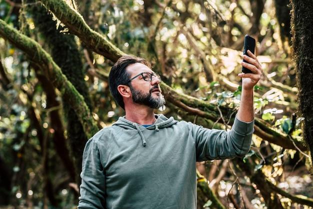 Volwassen man in het bos op zoek naar internettelefoonsignaal