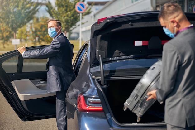 Volwassen man in pak en steriel masker stapt in de auto terwijl assistentie bagage in de kofferbak inpakt