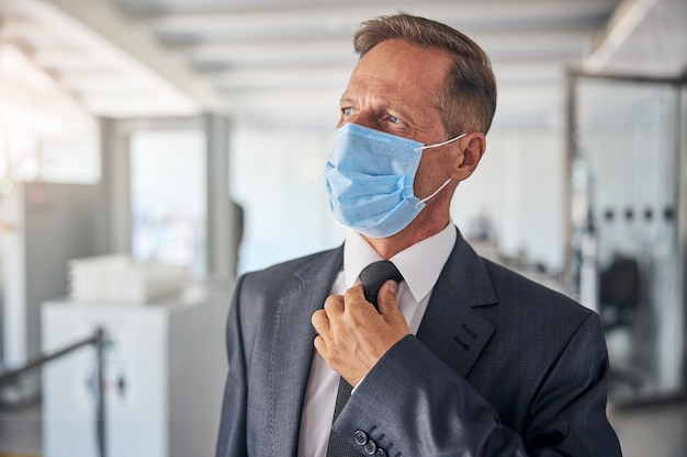 Volwassen man in pak en stropdas vliegt op reis tijdens pandemie en loopt op de luchthaven