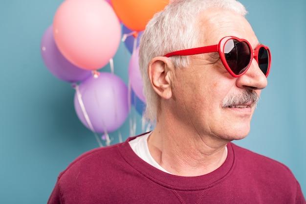 Volwassen man in stijlvolle zonnebril poseren op blauwe muur met kleurrijke ballonnen