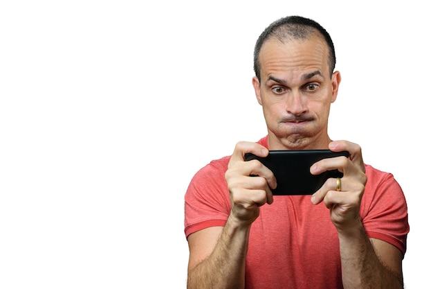 Volwassen man in vrijetijdskleding spelen op de smartphone en een grappig gezicht maken.