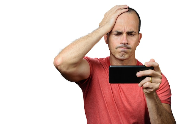 Volwassen man in vrijetijdskleding, teleurgesteld, met zijn hand liggend op zijn hoofd en smartphone horizontaal vast te houden.