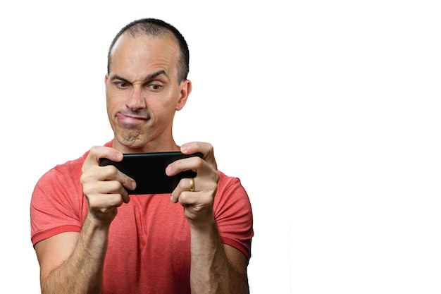 Volwassen man in vrijetijdskleding, zijn tong bijten, wenkbrauw opgetrokken en smarthphone horizontaal te houden.