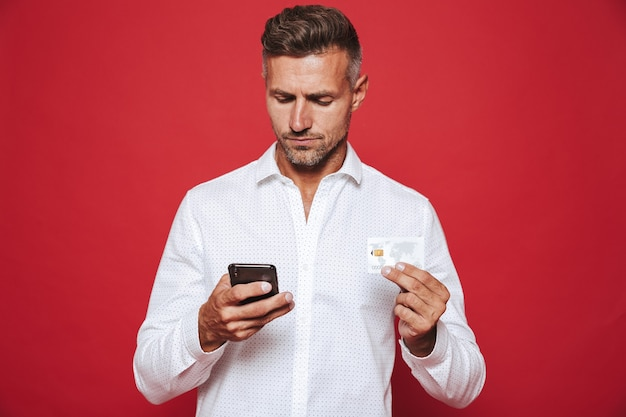 Volwassen man in wit overhemd met creditcard en smartphone geïsoleerd op rood
