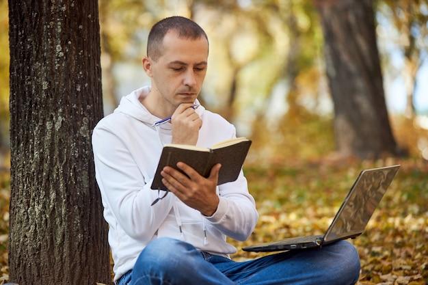 Volwassen man in witte hoodie studeert in park op laptop, schrijft in notitieboekje, leest boeken en studieboeken. buiten leren, social distancing