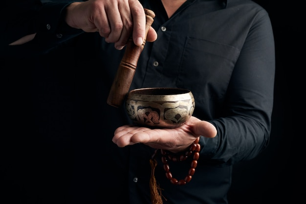 Volwassen man in zwart overhemd draait een houten stok om een koperen tibetaanse kom met water