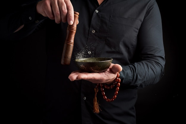 Volwassen man in zwart overhemd draait een houten stok om een koperen tibetaanse kom