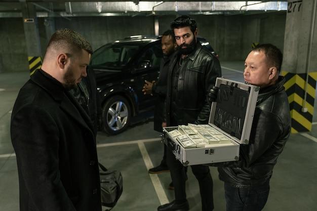 Volwassen man in zwarte jas, handschoenen en spijkerbroek koffer openen met stapels dollars terwijl ze worden getoond aan de moordenaar