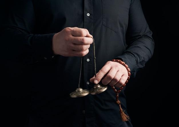 Volwassen man in zwarte kleding houdt in zijn handen een paar bronzen karatal aan een leren touw, object voor religieuze rituelen