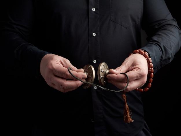 Volwassen man in zwarte kleding houdt in zijn handen een paar bronzen karatal aan een leren touw