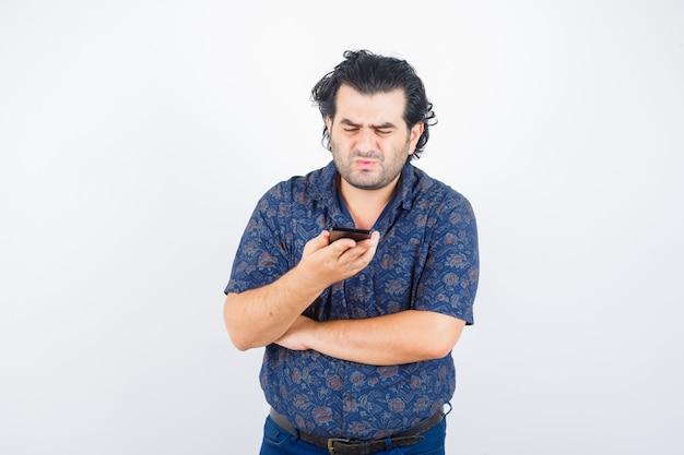 Volwassen man kijken naar mobiele telefoon in shirt en op zoek attent. vooraanzicht.