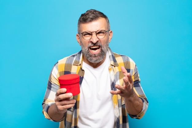 Volwassen man kijkt boos, geïrriteerd en gefrustreerd schreeuwend wtf of wat is er mis met je