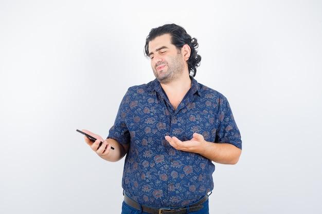 Volwassen man kijkt naar mobiele telefoon in shirt en kijkt mooi, vooraanzicht.