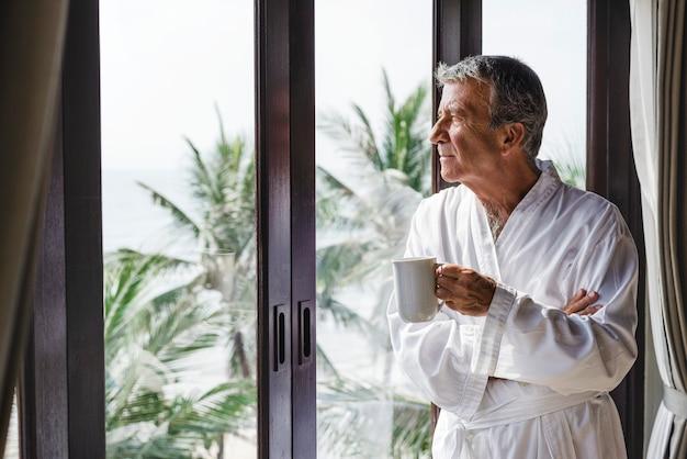 Volwassen man kijkt uit het raam van het hotel