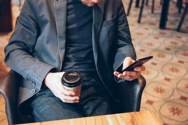 Volwassen man koffie drinken uit kartonnen beker en het gebruik van mobiele telefoon in cafe