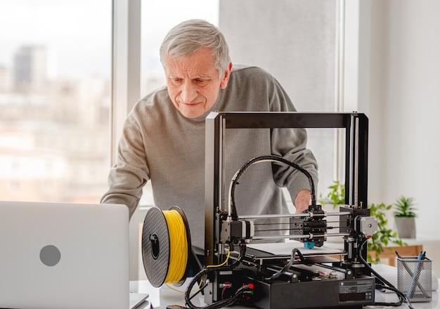 Volwassen man laptop kijken en moderne 3d-printer voorbereiden op werk
