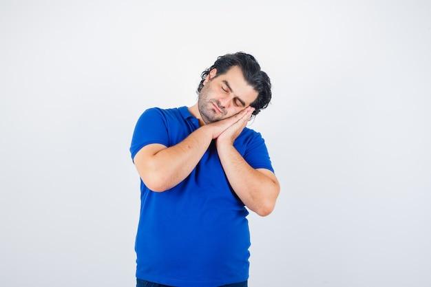 Volwassen man leunend op handpalmen als kussen in blauw t-shirt en op zoek slaperig, vooraanzicht.