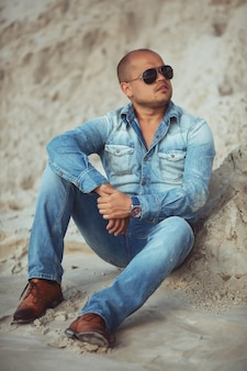 Volwassen man liggend in jeans kleding in het zand