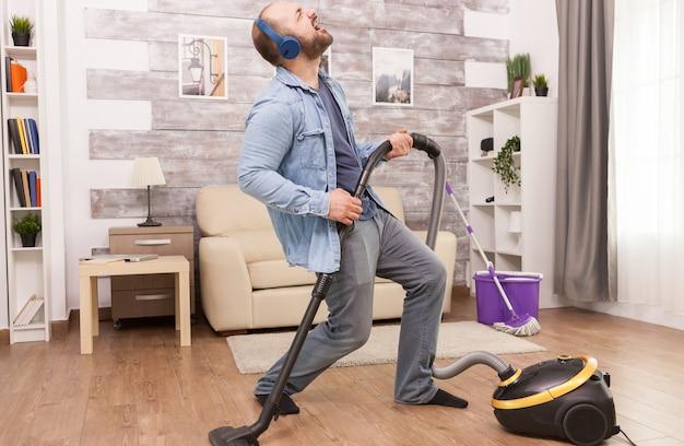 Volwassen man luistert naar rockmuziek op koptelefoon terwijl hij het huis schoonmaakt