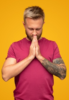 Volwassen man mediteren en bidden met handen samen