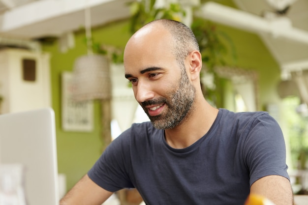 Volwassen man met baard terloops gekleed met behulp van moderne laptopcomputer, e-mail of berichten online controleren, zittend tegen groen interieur.