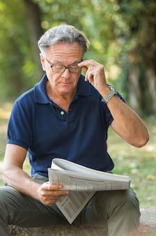 Volwassen man met bril tijdens het lezen van de krant in het park