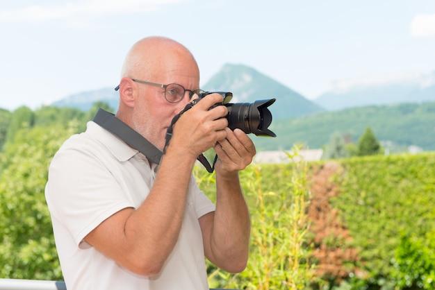 Volwassen man met dslr camera buitenshuis