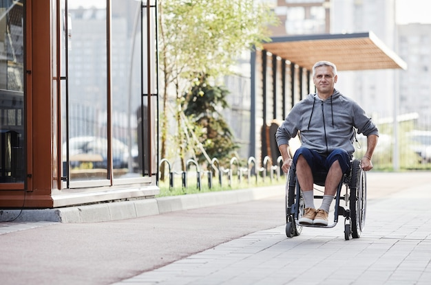 Volwassen man met een handicap die buiten in een rolstoel rijdt, hij loopt in de frisse lucht