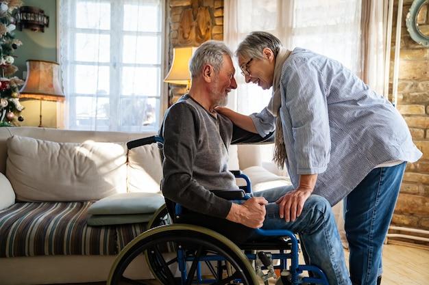 Volwassen man met een handicap in een rolstoel die plezier heeft met zijn vrouw. familie senior paar liefde concept