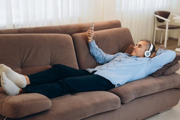 Volwassen man met grijs haar ligt op de bank en luistert naar muziek op zijn smartphone
