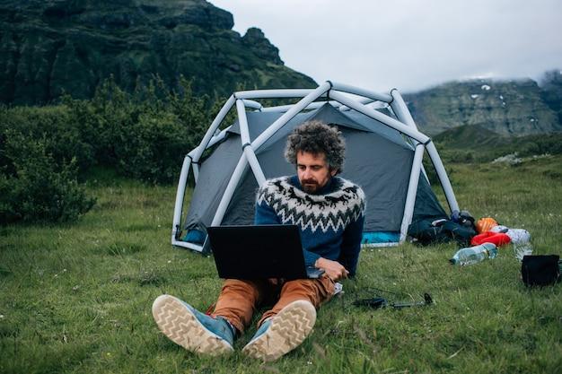Volwassen man met grijze baard en grappige hipster krulhaar zit voor camping tent op gras, werkt op afstand met laptop