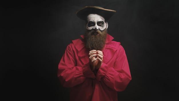 Volwassen man met lange baard verkleed als een griezelige kapitein op zwarte achtergrond.