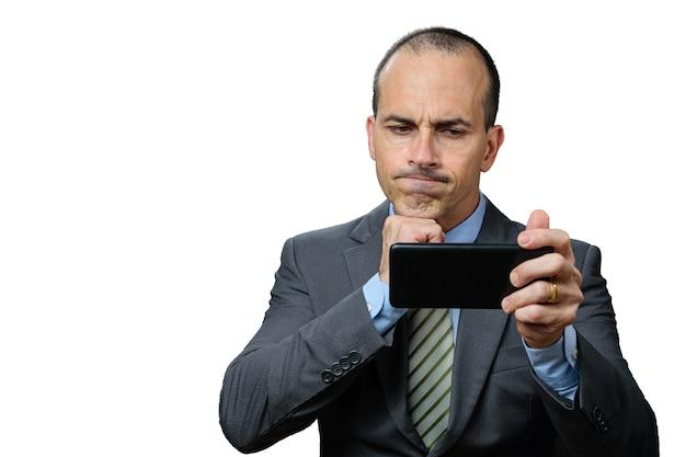 Volwassen man met pak en stropdas, kijkend naar zijn smartphone, teleurgesteld en met zijn vuist onder de kin.