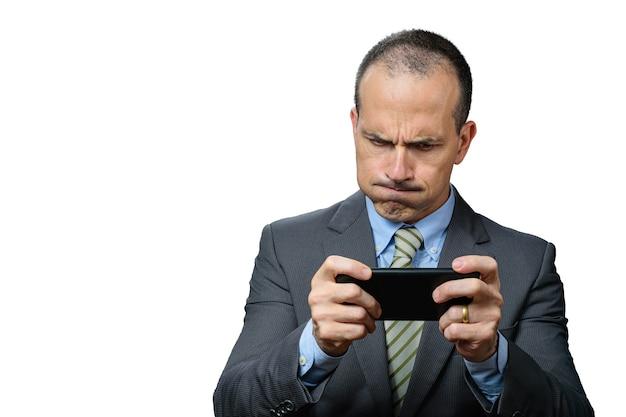 Volwassen man met pak en stropdas, spelen op zijn smartphone en ademen door zijn neus.