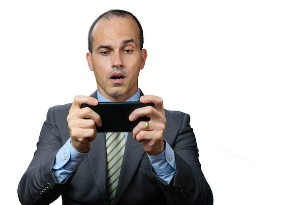 Volwassen man met pak en stropdas, spelen op zijn smartphone en met verbaasd gezicht.