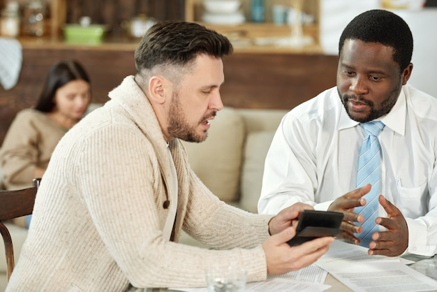Volwassen man met rekenmachine met bezoek van financieel adviseur zittend aan tafel en hypotheek bespreken