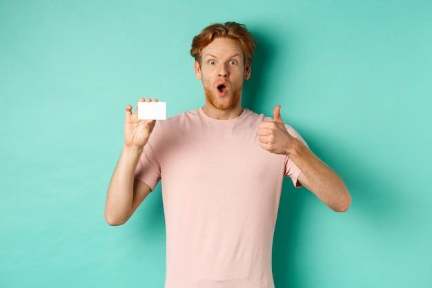 Volwassen man met rood haar en baard die plastic creditcard en duim omhoog toont, onder de indruk kijkt, raadt bank aan, die zich over muntachtergrond bevindt.