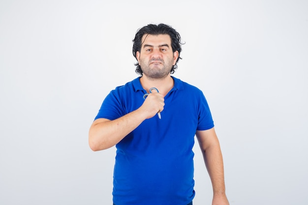 Volwassen man met schaar, lippen tuit in blauw t-shirt en op zoek agressief, vooraanzicht.